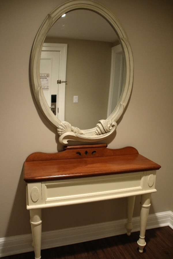 a small entryway table with a mirror