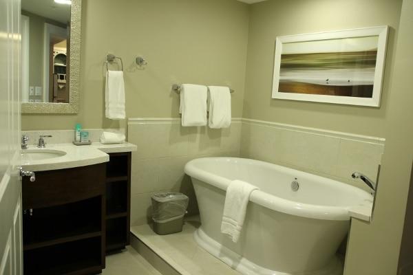a bathtub, sink, and mirror in a hotel bathroom