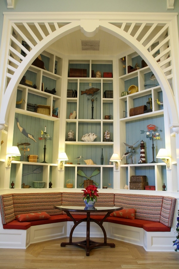 a large bookshelf with colorful knickknacks over a bench seating area