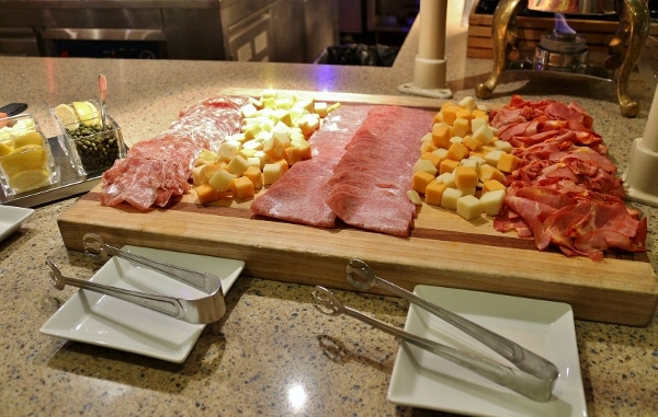 a variety of cold cuts and cheeses on a buffet