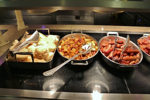 biscuits, home fries, and sausage on a buffet line