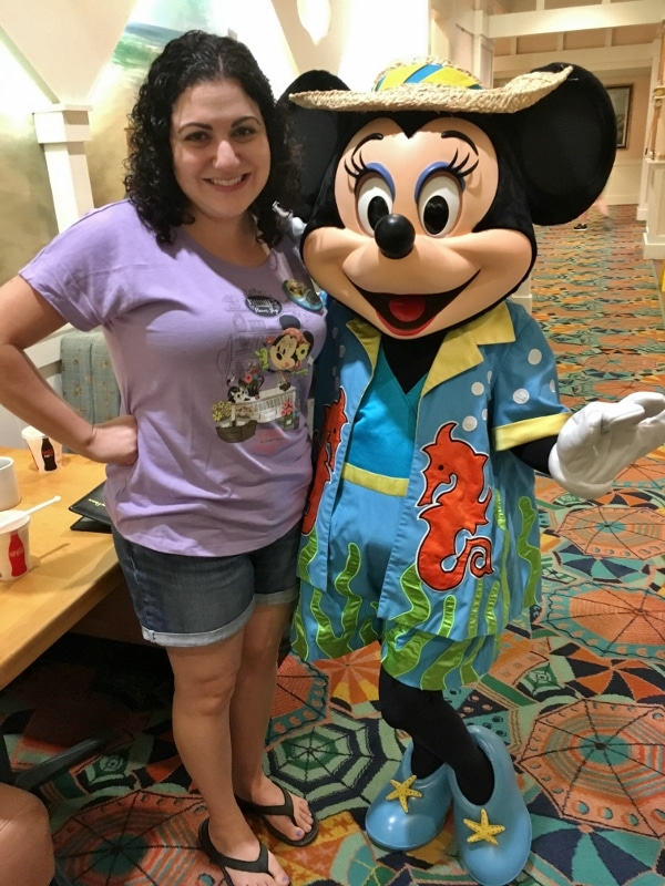 A woman posting with Minnie Mouse