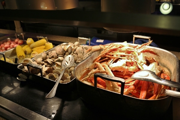 crab legs, steamed clams, and corn on the cob on a buffet
