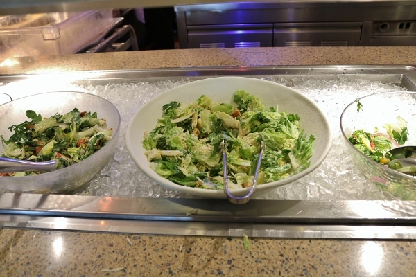 several green salads on a buffet