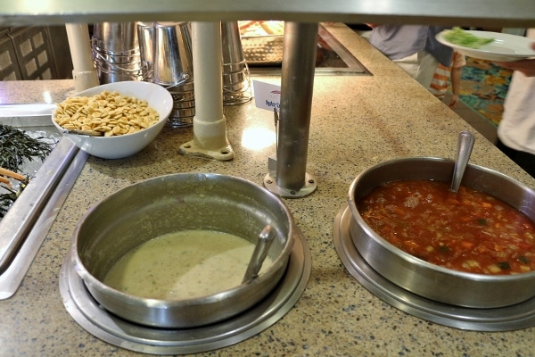 a couple pots of soup on a buffet