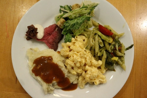 roast beef with salad, mashed potatoes, and pasta on a white plate
