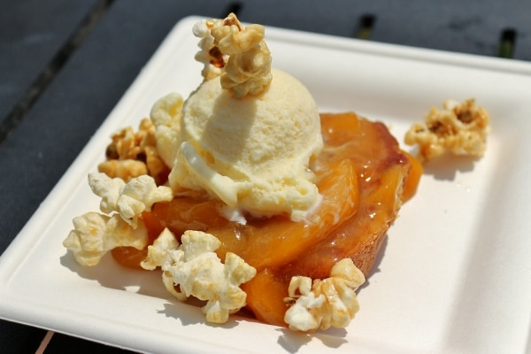 a plate of food with peaches, ice cream, and popcorn