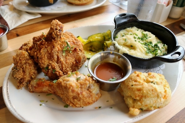 a plate of fried chicken with mashed potatoes and a biscuit