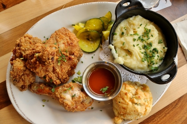 overhead view of a plate of fried chicken with mashed potatoes and hot honey