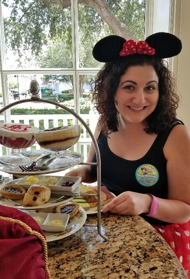 A woman sitting at a table with a plate of food at afternoon tea
