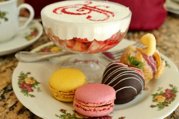 macarons and a chocolate covered strawberry on a dish