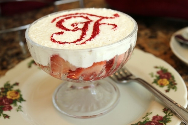 side view of a glass dish of strawberries and cream