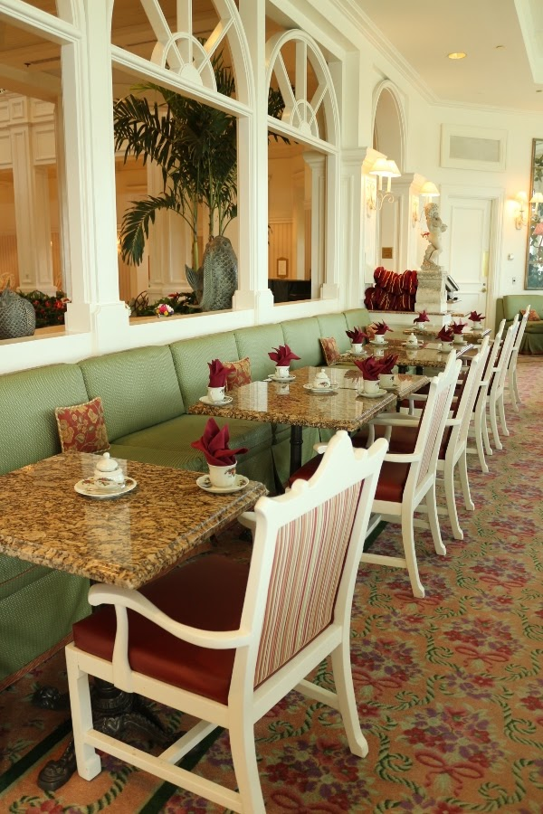 tables in a tea room topped with tea cups