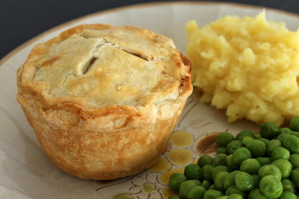 An individual pie on a rustic plate with mashed potatoes and peas on the side.