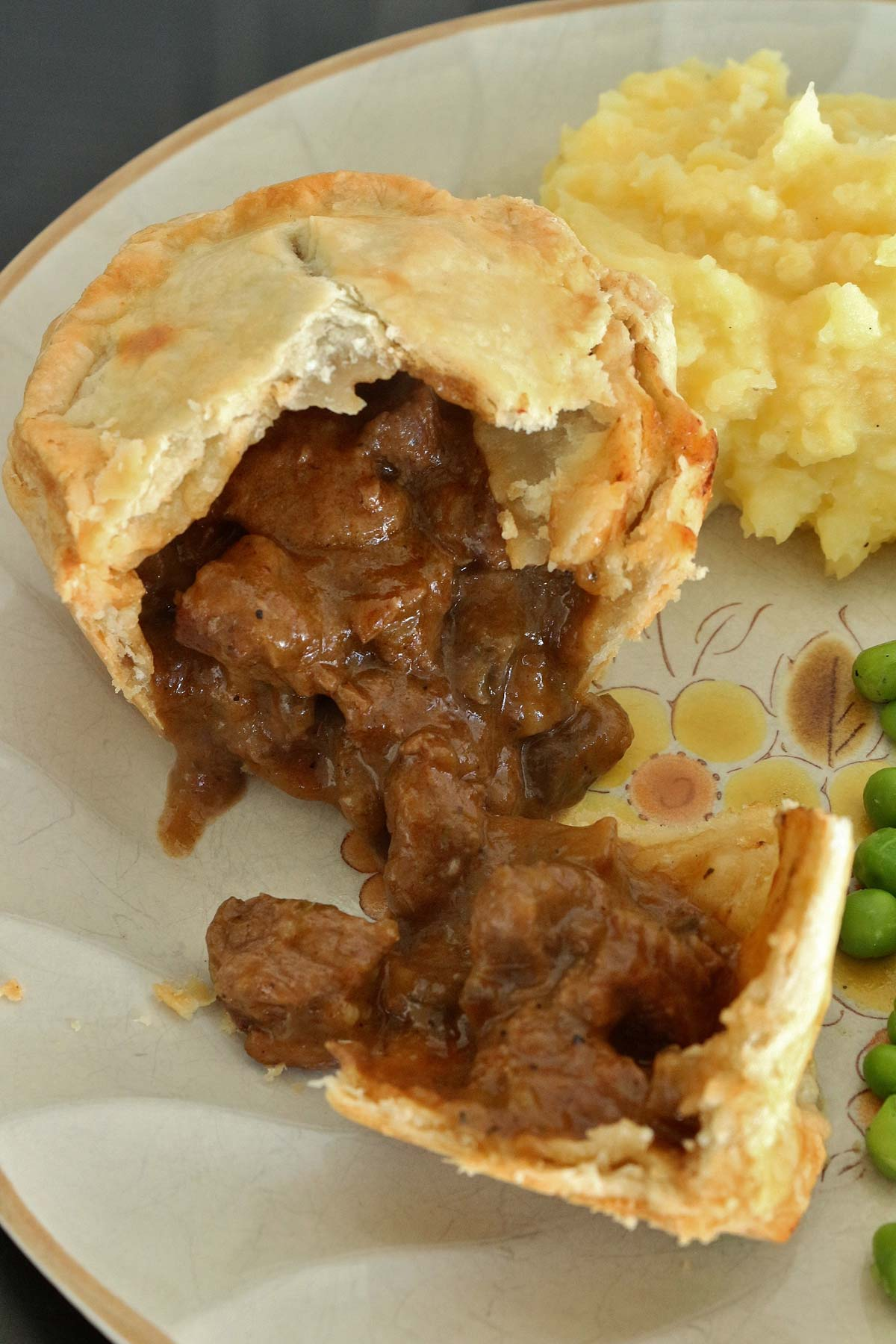 A small pie broken open on a plate with beef and mushroom filling spilling out.