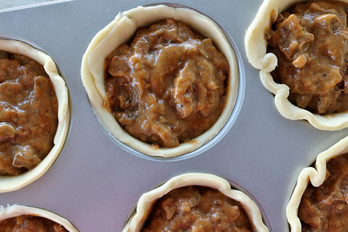 Closeup of a jumbo muffin pan lined with pastry dough and filled with beef stew.