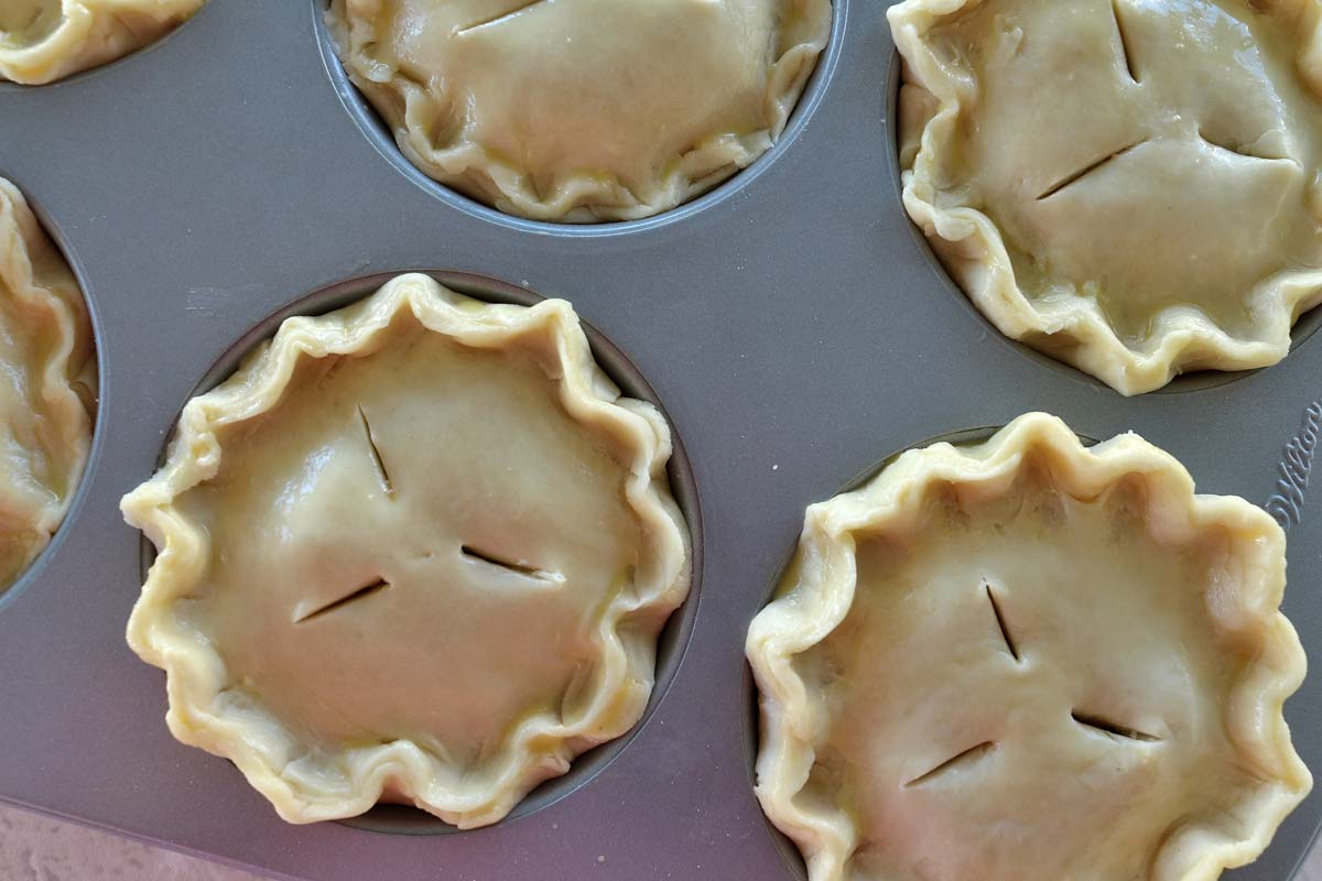 Individual unbaked pies with crimped edges assembled in a jumbo muffin pan.