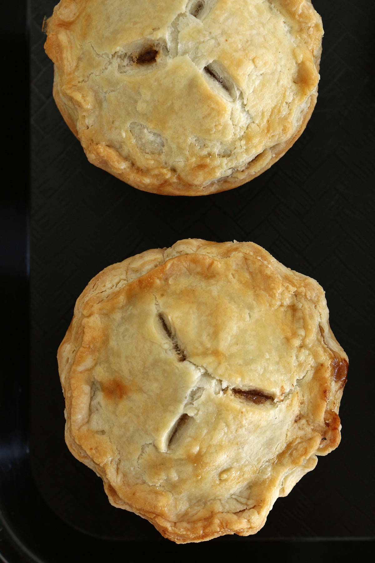 Two baked mini pies with crimped edges and 3 vents on a black background.