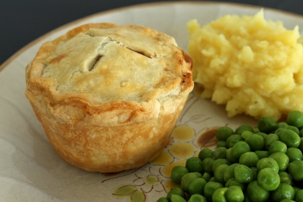 Individual pie with mashed potatoes and peas on the side.