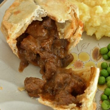 an individual beef and mushroom pie cut open with the filling pouring out