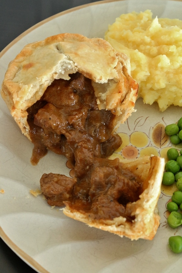 overhead view of an individual beef and mushroom pie cut open to show filling