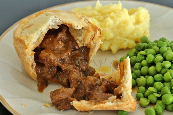 Individual beef and mushroom pie cut open with the filling pouring out
