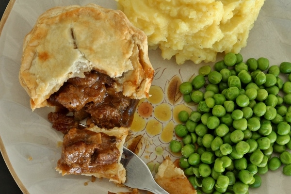 overhead view of a small beef pie with peas and mashed potatoes