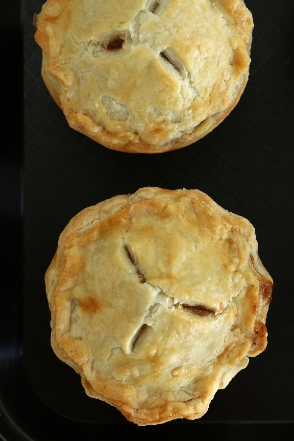 Overhead view of 2 individual sized pies with 3 vents each on a black tray