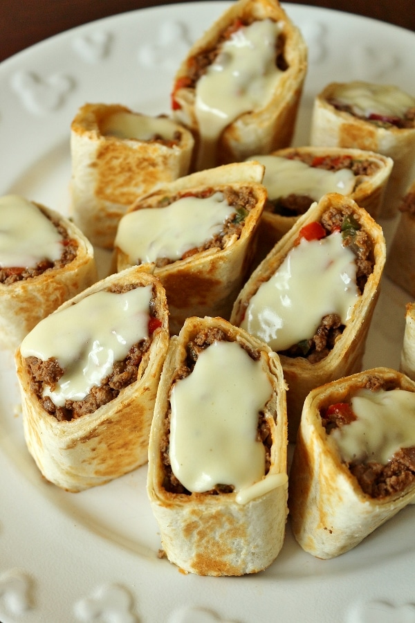 A platter of Mexican hot pockets: tortillas with beef filling, and cheese sauce on top