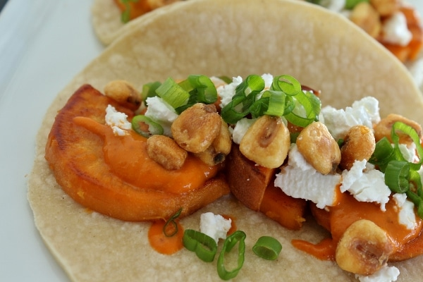 Sweet potato tacos with almond salsa, crumbed feta cheese, corn nuts, and scallions