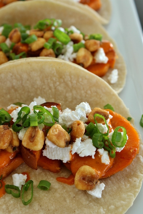 Close up of sweet potato tacos with almond salsa, crumbed feta cheese, corn nuts, and scallions