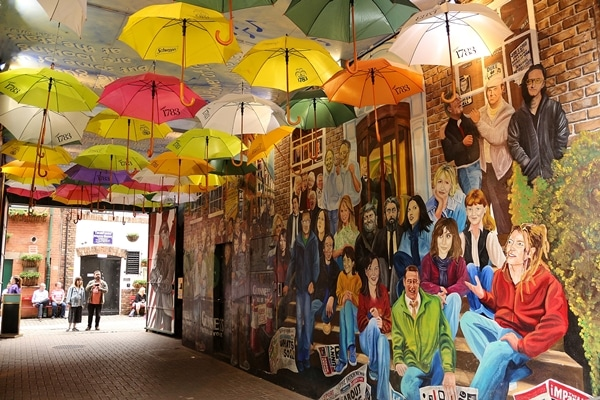 umbrellas hanging in a tunnel painted with murals