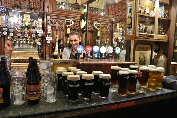 a bar lined with glasses of Guinness and other beer