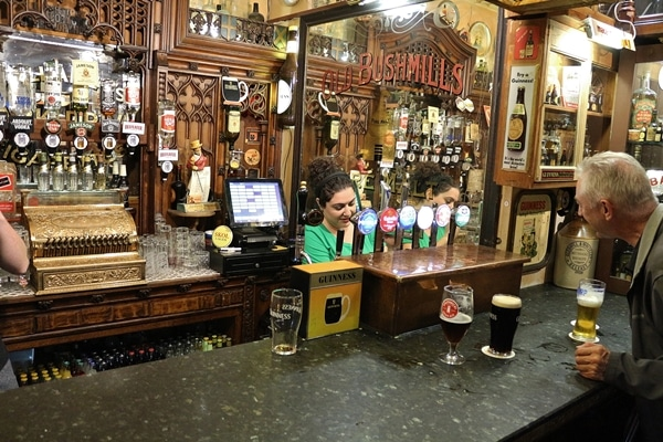 A person standing behind the bar filling a drink