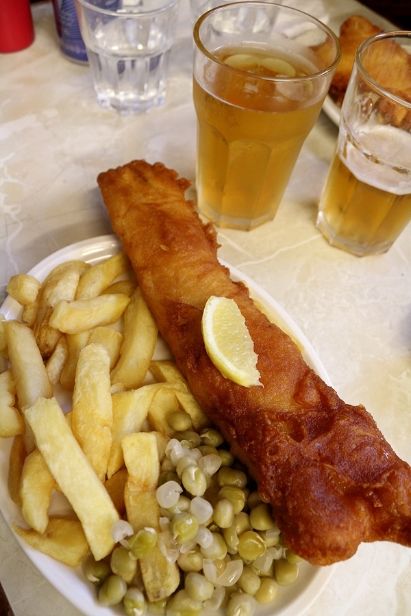 a plate of fish and chips with peas, and glasses of beer