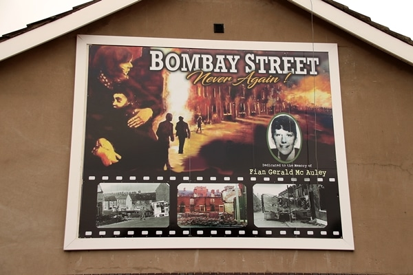 A sign on the side of a building that says Bombay Street Never Again!