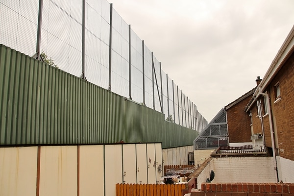 the backs of residential buildings butting up against the Peace Wall in Belfast