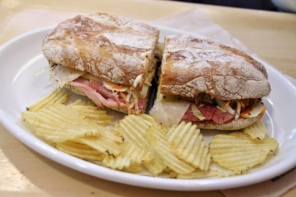 A sandwich cut in half on a plate with potato chips