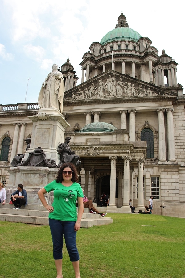 A person posing in front of Queen Victoria\'s statue and Belfast City Hall