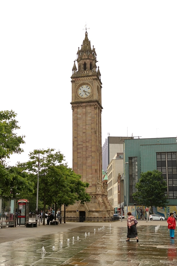 a large clock tower with a fountain in front