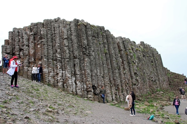 A group of people walking up a hill with a rocky wall