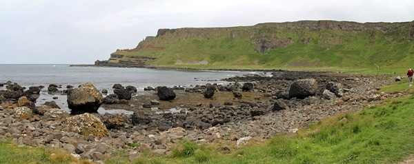 A rocky shoreline with cliffs in the distance