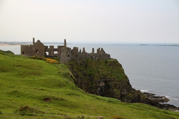 castle ruins on a grassy hill overlooking the sea