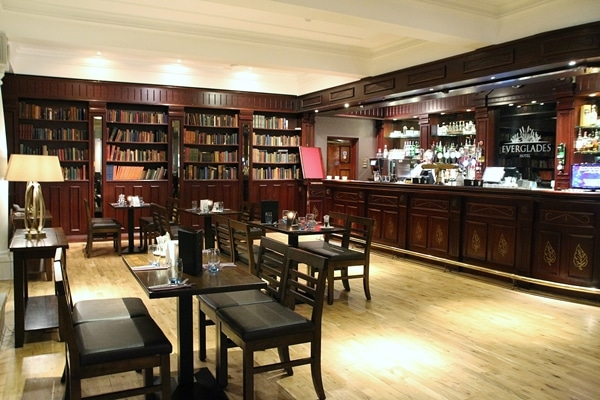 a hotel lounge bar with many bookshelves