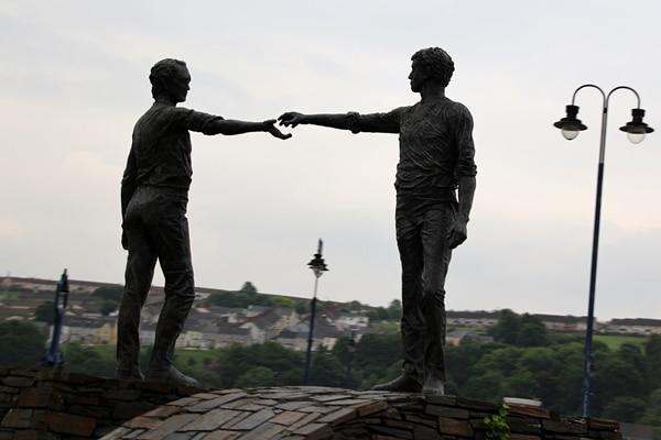 a statue of 2 people reaching out to each other