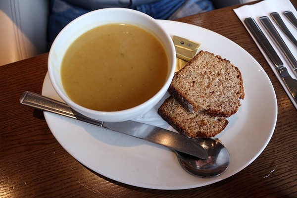 a bowl of soup with brown bread