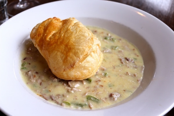 A bowl of stew with puff pastry on top