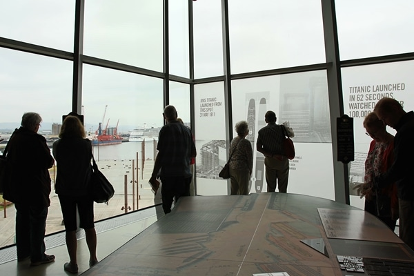 A group of people standing in a room with large windows
