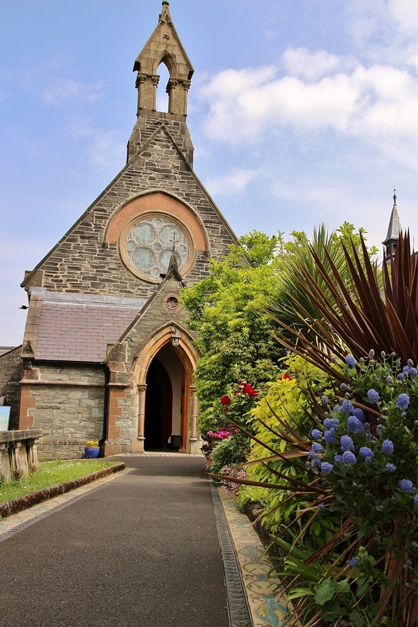 A stone church with flowers in front
