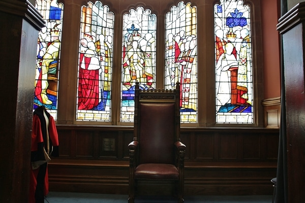 A big chair in front of stained glass windows